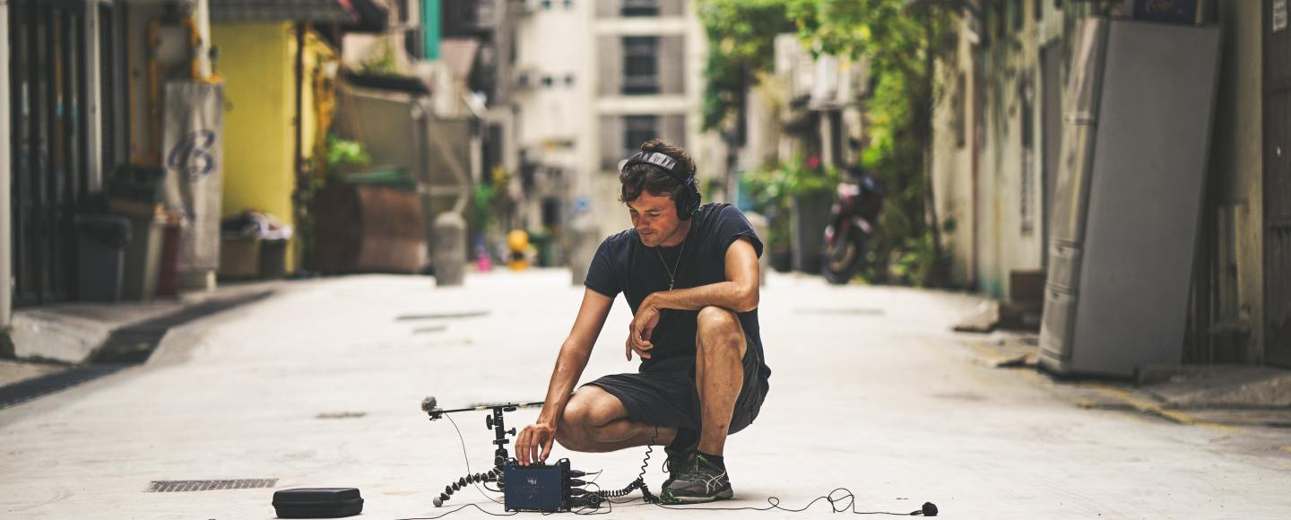Person crouched in the street recording ambient sounds.