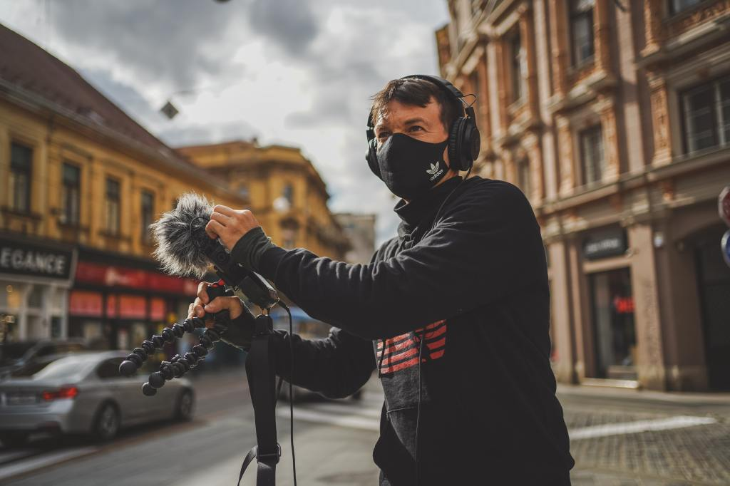 Person in street using field recording equipment.